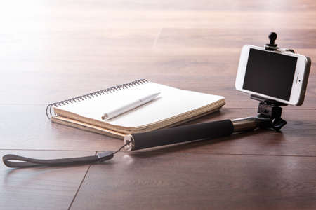 Selfie stick with smartphone and notepad on wooden surface