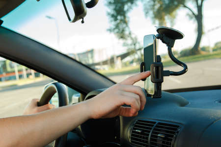 Male hand and smartphone in a car