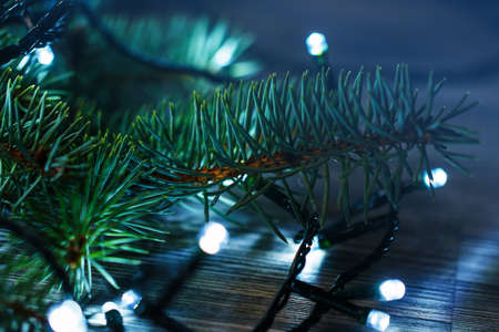 christmas lights and branches of spruce on wooden surface stock photo 47668067