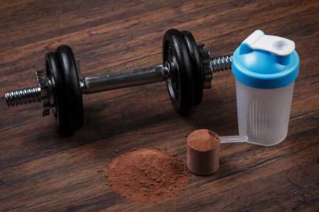 albumin: Heavy black dumbell and protein powder