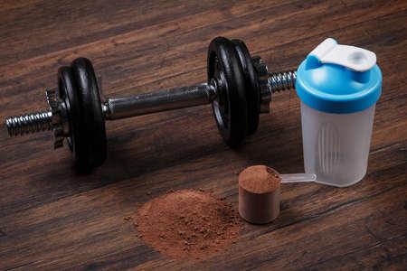 Lourd haltère noir et poudre de protéine
