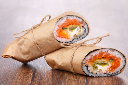 burrito: Sushi burrito - new trendy food concept. Sushi burrito rolls on wooden surface