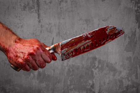 hold hand: Male hand with bloody knife over concrete wall