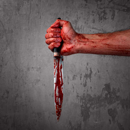 carnage: Male hand with bloody knife over concrete wall