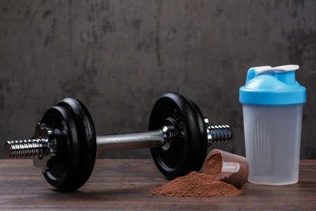 重い黒のダンベルとタンパク質粉末