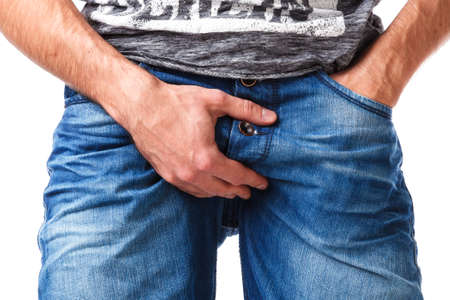 Man in jeans put his arm on groin