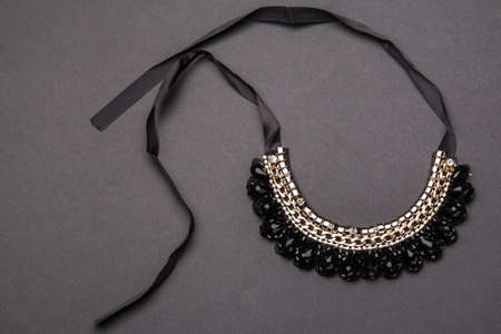 lavish: Necklace with black stones on gray background