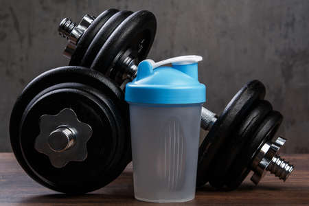 muscle gain: Dumbbells and shaker for protein cocktail