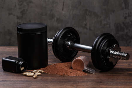 casein: Dumbells and food supplements on the table Stock Photo