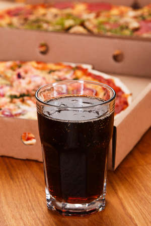 coke: Glass of coke and pizza on the table