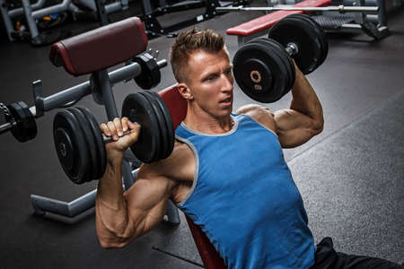 man exercise: Muscular man training his shoulders with dumbbells Stock Photo