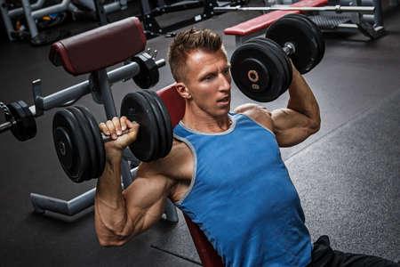 Muscular man training his shoulders with dumbbells Standard-Bild
