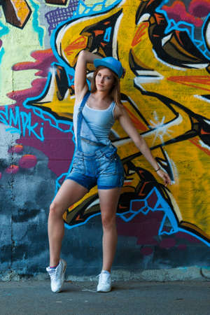 overalls: Young girl in denim overalls posing against wall with graffiti Stock Photo