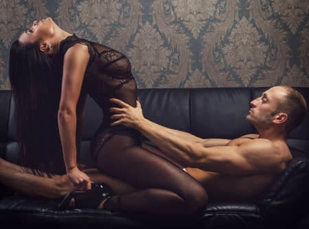 sexo pareja joven: pareja sexy en ropa interior en el sof� de cuero