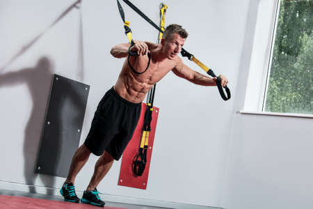 Muscular guy and suspension straps in gym 스톡 콘텐츠