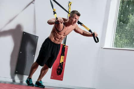 Muscular guy and suspension straps in gym Standard-Bild