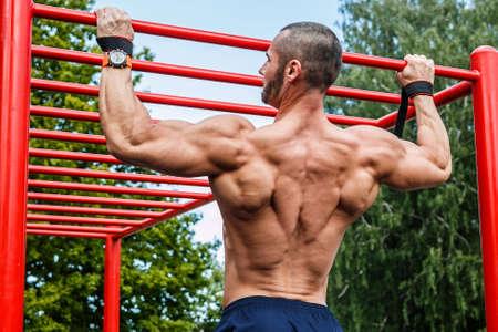 Muscular man doing pull-ups on horizontal bar Standard-Bild