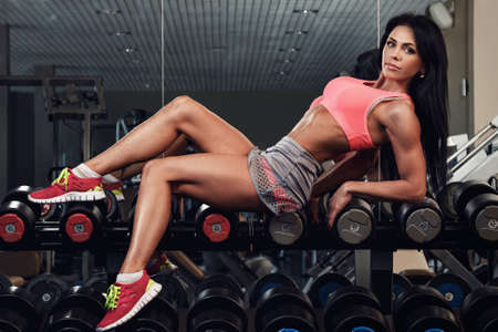laying abs exercise: Young and beautiful girl with sexy body in the gym