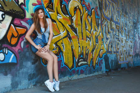 rnb: Young girl in denim overalls posing against wall with graffiti Stock Photo