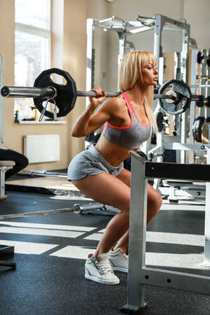 quadriceps: Beautiful blonde during workout in gym Stock Photo
