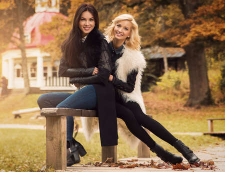2 november: Two beautiful girls friends in autumn park Stock Photo