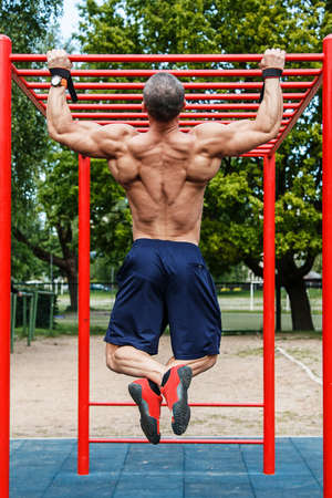 Muscular man doing pull-ups on horizontal bar Stock Photo