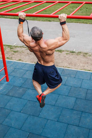 gripping bars: Muscular man doing pull-ups on horizontal bar Stock Photo
