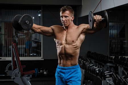 muscle training: Muskulöser Mann mit den Schultern mit Hanteln trainieren