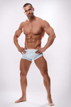 ropa interior: Hombre hermoso que presenta en ropa interior sobre fondo blanco