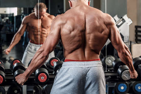 latissimus: Young man showing his muscular back in the gym