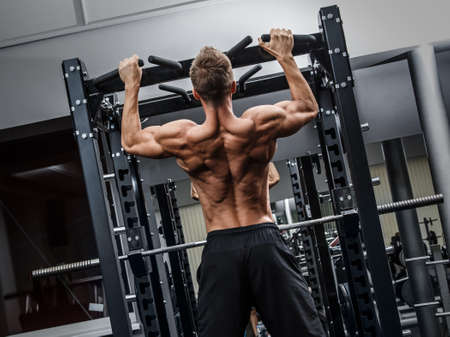 Muscular man training his back in gym