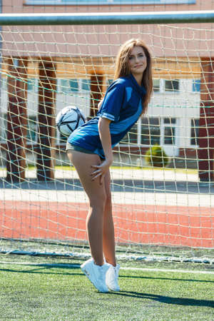 summer sport: Beautiful girl with ball on the soccer field