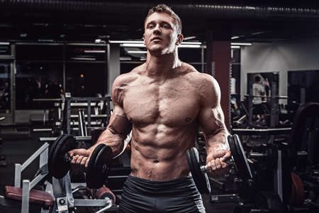 Muscular man with dumbbells in gym Stockfoto