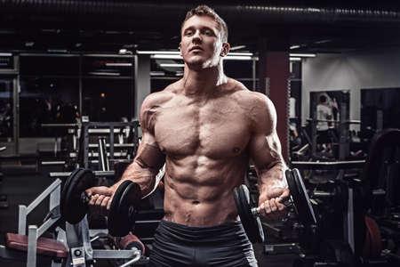 hombre deportista: Hombre muscular con pesas en el gimnasio