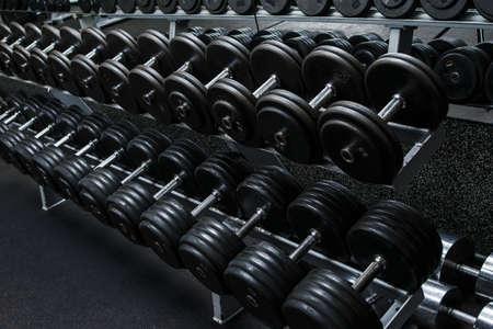 Various dumbbells in gym Foto de archivo