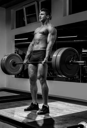 Strong man doing deadlift  in gym