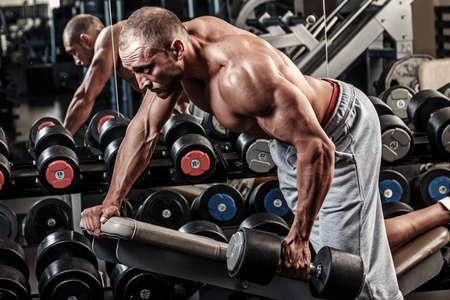 latissimus: Muscular man working out in gym