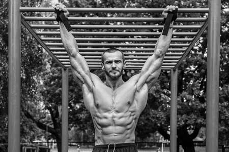 and the horizontal man: Muscular man doing pull-ups on horizontal bar Stock Photo