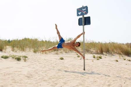 nudist young: Man doing human flag exercise on pole