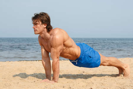 athletic body: Muscular man during workout on the beach