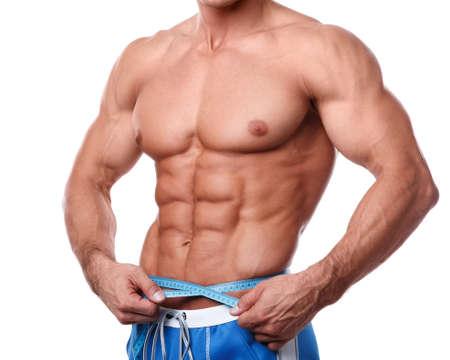 waistline: Man measuring his waistline over white background