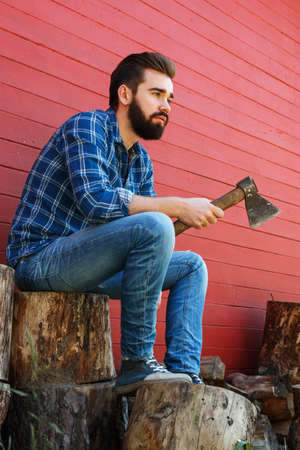 Handsome bearded man with axe sitting on stump