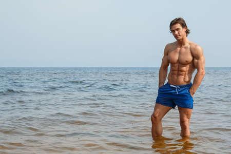 niño sin camisa: Guapo y musculoso hombre en la playa