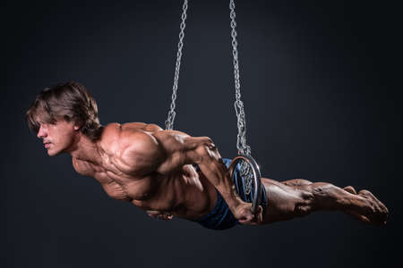 Athlete man: Fuerte y musculoso chico gimnasta en los anillos