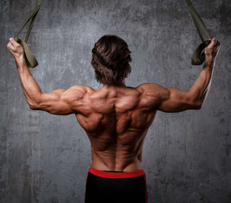 hang body: Muscular man during workout with suspension straps Stock Photo