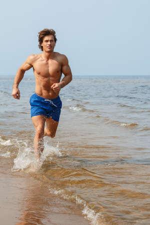 Homme musculaire pendant le jogging près de la côte de la mer Banque d'images - 74653934