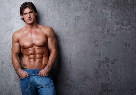 sin camisa: Hombre hermoso del músculo en los pantalones vaqueros