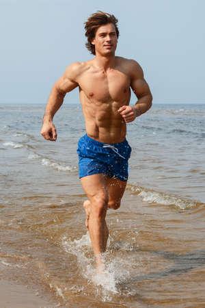 Homme musclé pendant le jogging par la côte de la mer Banque d'images - 56635051