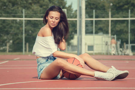 sitting on the ground: Sexy girl lying on the basketball field
