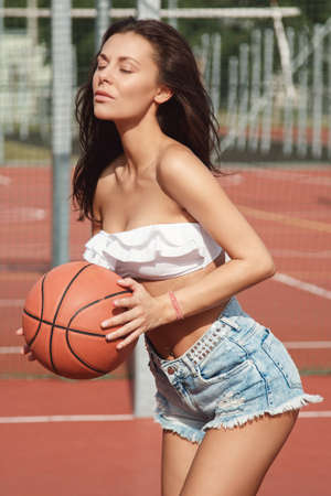 navel piercing: Sexy woman with on a  basketball playground Stock Photo